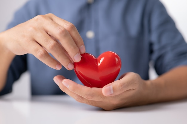 Male hands holding red heart world mental health day life and health insurance