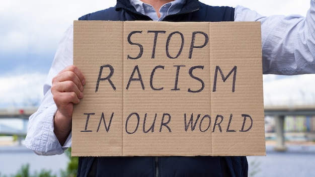 Male hands holding a sign about racism