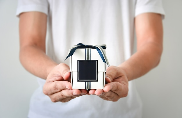 Male hands holding a small white gift box wrapped with blue and silver color ribbon and dark blue blank label