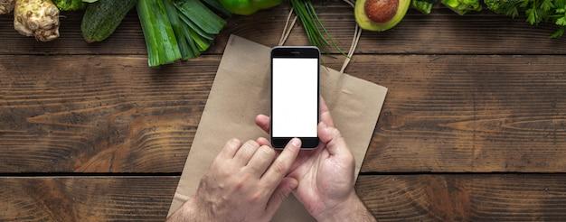 テキストメッセージまたは緑緑野菜のデザインの空白の画面を持つスマートフォンを保持している男性の手。モバイル携帯電話アプリケーションのコンセプトを介した食品注文