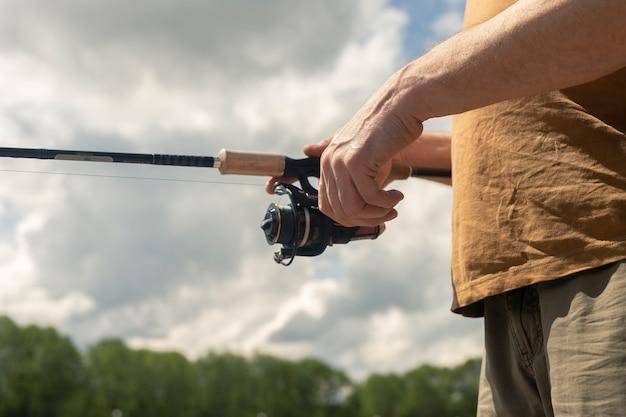 スピニングリールロッドまたはスプーンベイトを保持し、マス、クローズアップのための釣りをしている男性の手。空と背景の木々。