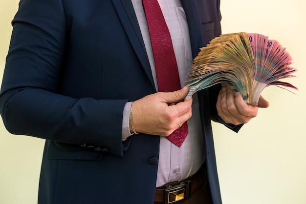 緑に分離されたウクライナグリブナ紙幣のスタックを保持している男性の手。グリブナの新しい1000500および200uah紙幣。お金を節約するコンセプト