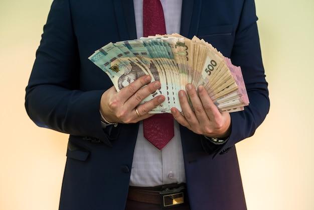 Мужские руки, держа стопку банкнот украинской гривны, изолированные на зеленом. новые 1000 гривен банкноты 500 и 200 грн. экономьте деньги концепции