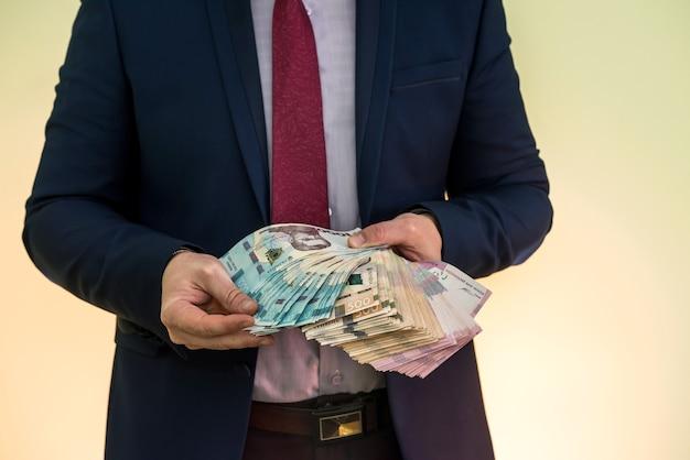 緑に分離されたウクライナグリブナ紙幣のスタックを保持している男性の手