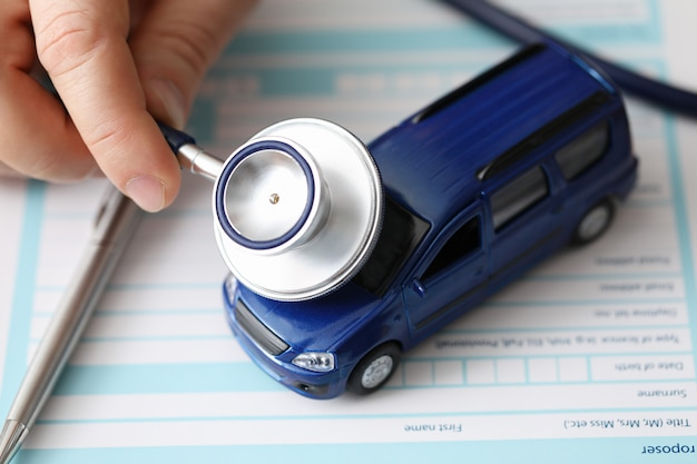 Male hands holding stethoscope toy car, checking