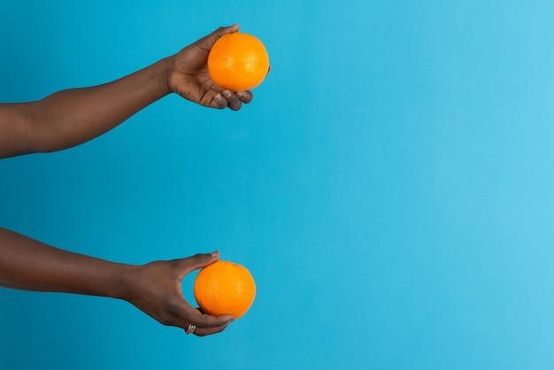 Мужские руки держат два оранжевых плода у синей стены