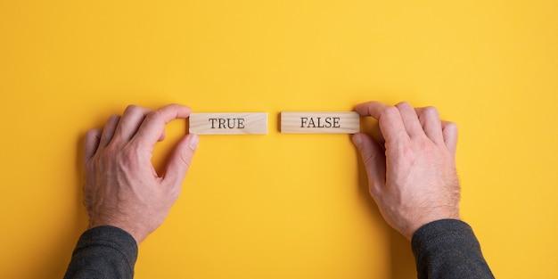 Мужские руки держат два деревянных колышка со знаком «истина» на одном и «ложь» на другом.