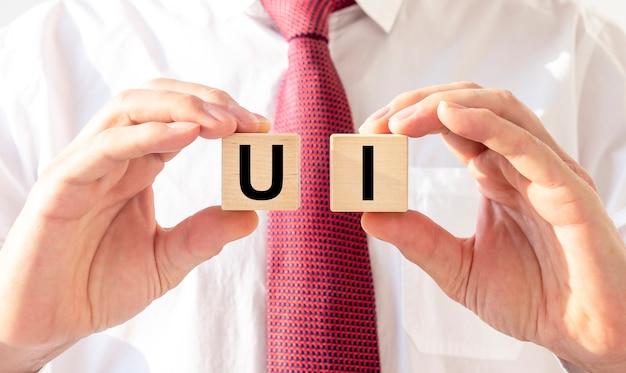 Uiの頭字語、ダイスの碑文を保持している男性の手。