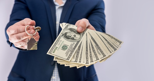 Male hands  holding us dollars bills and house key isolated. concept buy or real estate loan