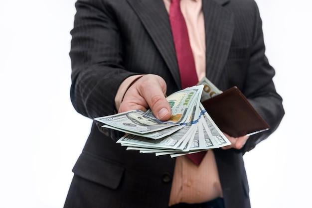 ドル紙幣でいっぱいの財布を持っている男性の手がクローズアップ