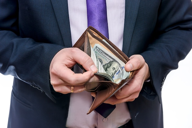 Мужские руки держат бумажник, полный долларовых банкнот, крупным планом