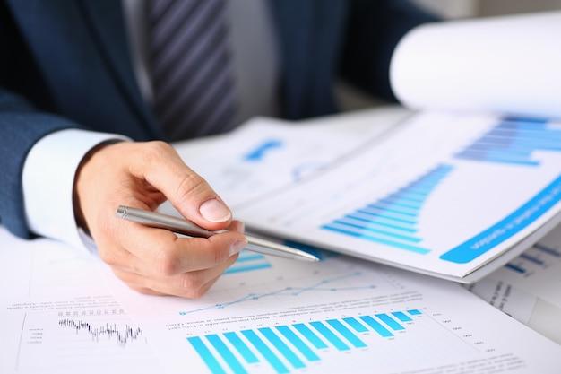 Мужской руки держит документы с финансовой статистикой на крупном плане рабочего пространства офиса.