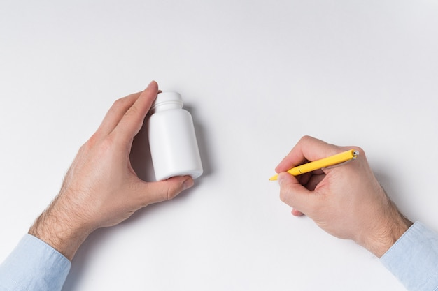 Male hands holds pill bottle and pen. doctor writes prescription concept. top view