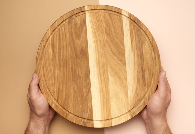 Male hands holds round empty wooden pizza board, top view