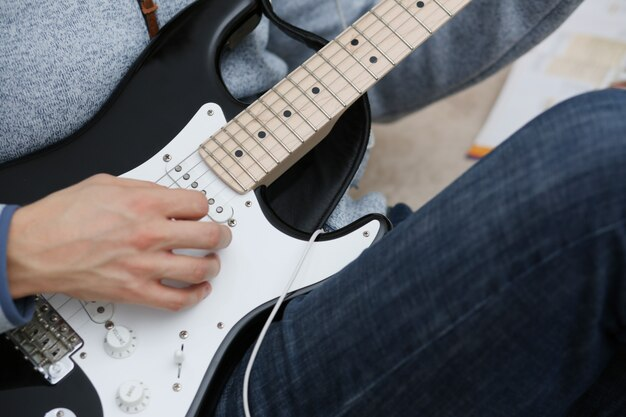 Male hands at home play and tune the electric guitar is engaged in music realizes listening enjoying music notation large concept closeup