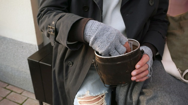 Male hands of a homeless old man holding a bowl, a glass for donations