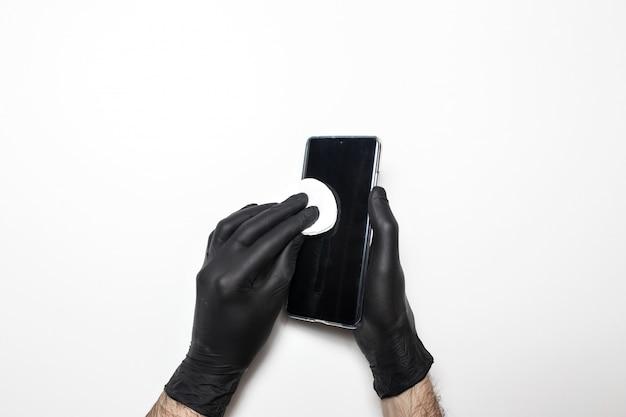 Мужские руки в черных медицинских перчатках дезинфицируют экран телефона. белый изолированный фон.