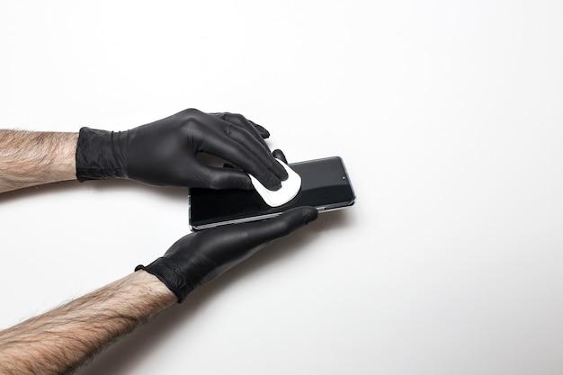 Мужские руки в черных медицинских перчатках дезинфицируют экран телефона. белая изолированная стена.