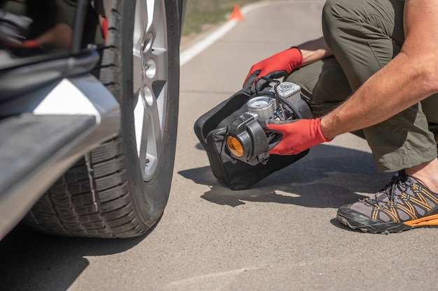 Мужские руки в перчатке и переносной шиномонтажный насос для накачивания автомобильного колесного компрессора с воздушным компрессором ...