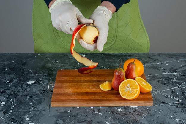 Мужские руки в перчатках, очищающие красное яблоко на мраморном столе.