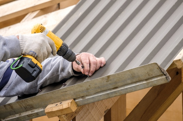 Мужские руки в перчатках отверткой прикручивают кровельный лист к крыше