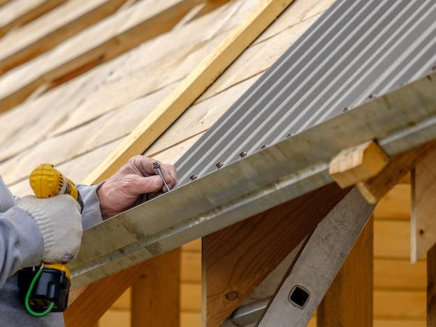 스크루드라이버가 있는 장갑을 끼고 지붕 시트를 지붕에 나사로 고정하는 남성 손