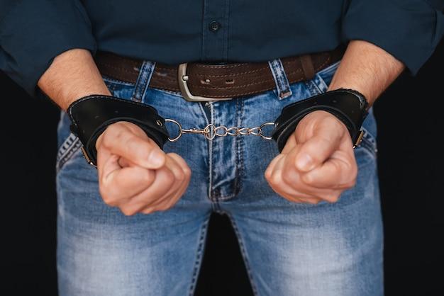 Мужские руки в кожаных наручниках для бдсм-секса