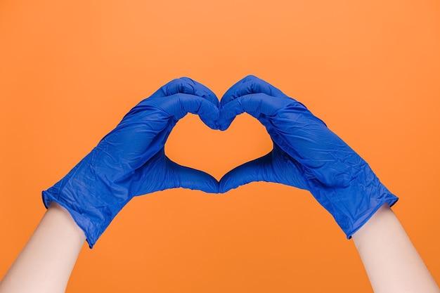 심장 기호를 만드는 의료 장갑에 남성 손