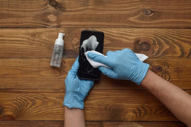 Мужские руки в медицинских перчатках обрабатывают телефон антисептиком.
