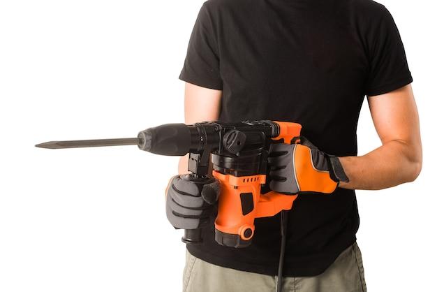Мужские руки в защитных перчатках держат новый большой электрический перфоратор