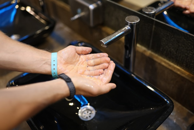 流水で石鹸の泡で男性の手