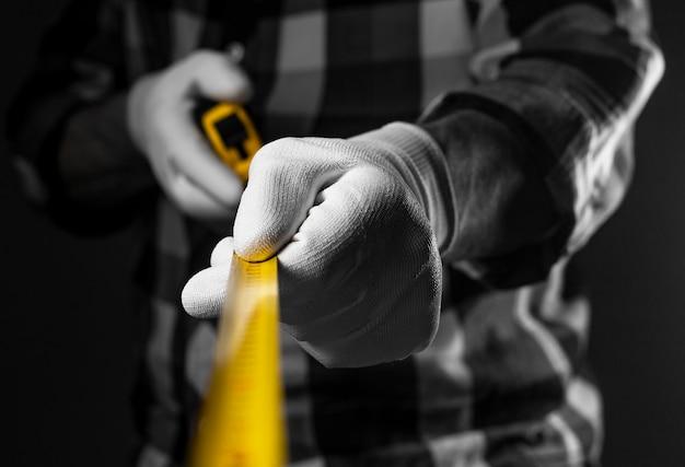 Мужские руки в белых строительных перчатках, держа желтый выдвижной инструмент рулетки, распространяются на камеру, крупным планом.