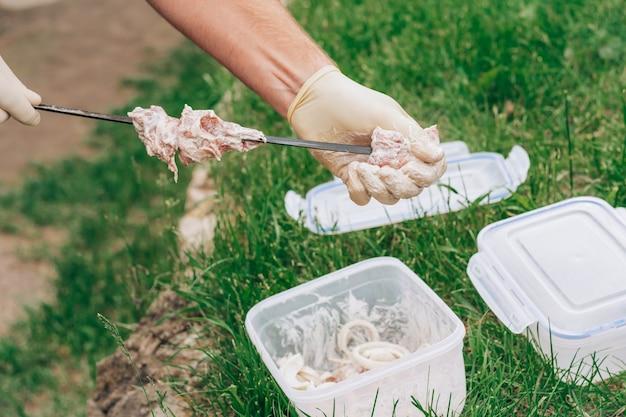 Мужские руки в белых перчатках нанизывают сырое мясо в маринаде на шпажки, для приготовления шашлыка