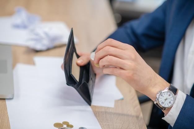 作業台の上の黒い財布にコインを折りたたむ腕時計の男性の手