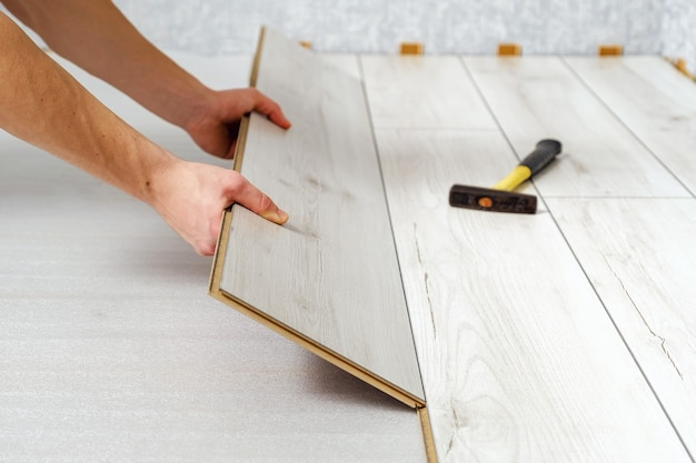 Male hands is laying wooden panel of laminate floor indoors close-up. laminate flooring, copy space