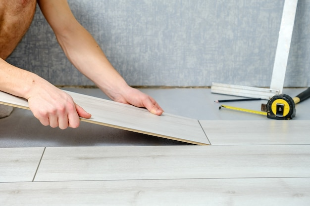 男性の手は、ラミネート床の木製パネルを屋内のクローズアップに置いています。ラミネートフローリング、コピースペース