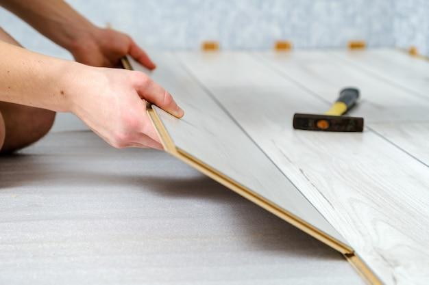 男性の手は、ラミネート床の木製パネルを屋内のクローズアップに置いています。ラミネートフローリング、セレクティブフォーカス