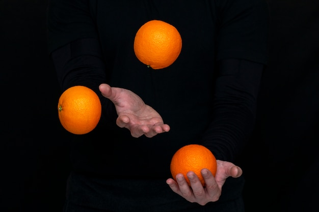 Male hands juggle with fresh oranges on a dark wall