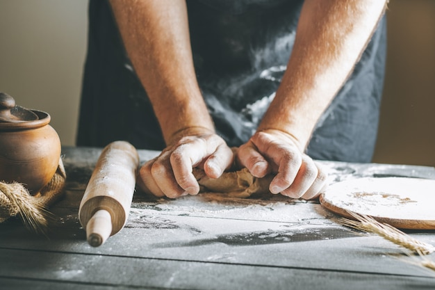 Male hands knead dough with flour next to clay pot and oil bottle and rolling pin on dark table, while cooking