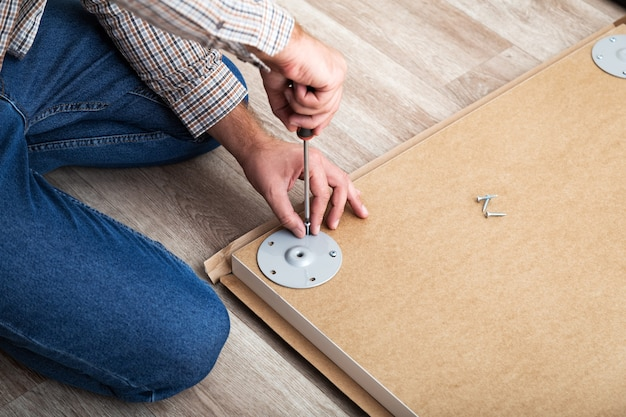 Male hands master collects table furniture using screwdriver tools, instrument at home. furniture assembly using screwdriver. moving, home improvement, furniture repair and renovation.