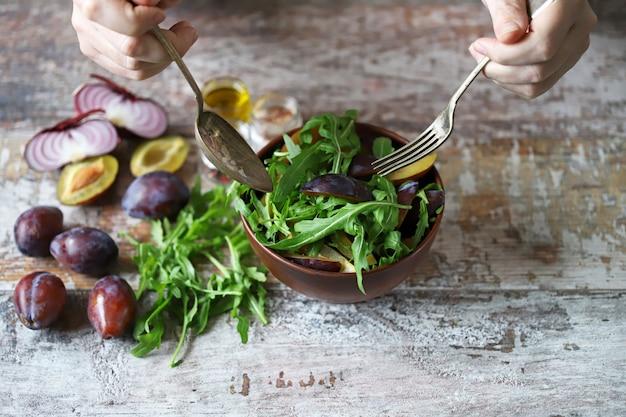 Мужские руки смешать салат в миску с ложкой и вилкой.