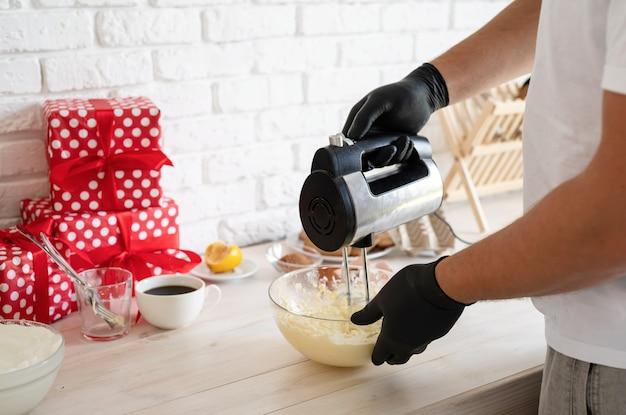 キッチンのクローズアップで生地と電気ミキサーを混合する男性の手