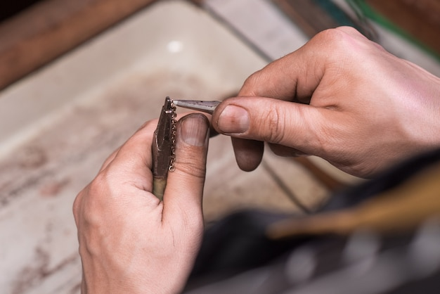 金の鎖を織り上げる宝石商の男性の手。チェーン作成プロセス