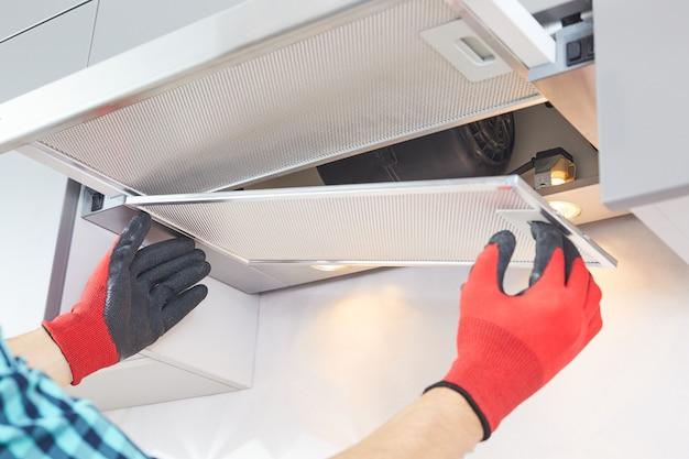 電気技師の男性の手がレンジフードのトラブルシューティングを行います。炊飯器フードの修理。キッチン家具のホームレンジフードを組み立てる労働者。