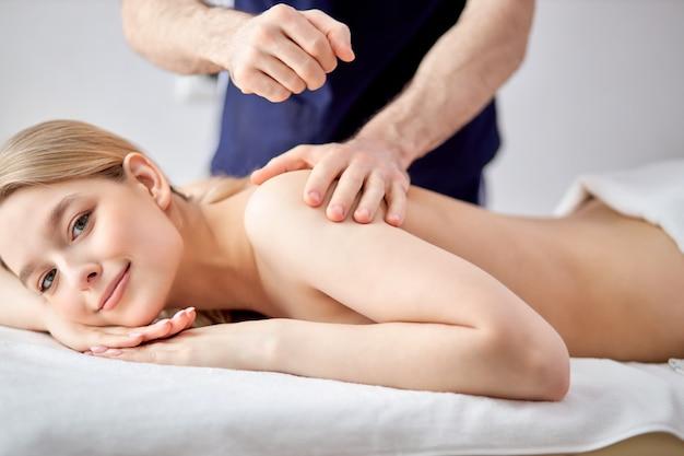 마사지 치료사의 남성 손은 미용실에서 예쁜 여성에게 가벼운 마사지를 합니다.