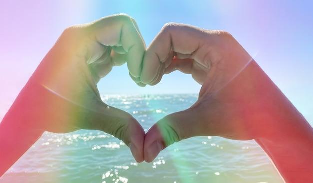 바다 배경에 있는 남성의 손은 사랑을 상징하는 하트 모양으로 접혀 있습니다. 로맨스와 관계 개념입니다.