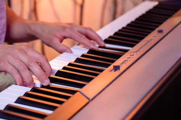 美しい色の背景にピアノの鍵盤の男性の手がクローズアップ。