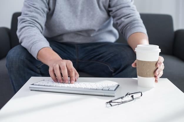 Мужские руки или мужчины служащий, набрав на клавиатуре с кофе