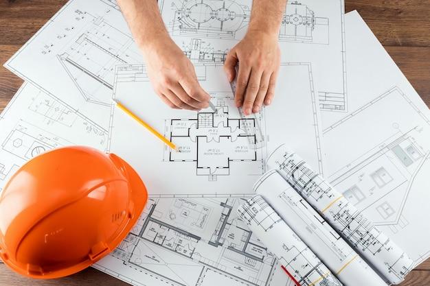 Male hands, orange helmet, pencil, architectural construction drawings, tape measure.