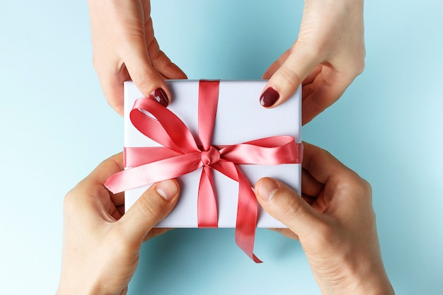 Male hands passes gift box to female hands